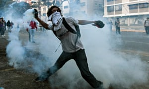 A student protester throws back a teargas canister during demonstrations in Caracas