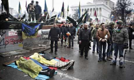 Bodies lay on the ground surrounded by fellow anti-government protesters during clashes in Kiev