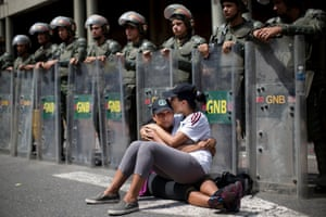 Women sit in front of a line of National Bolivarian Guard outside the Palace of Justice court where opposition leader Leopoldo López is due on charges of inciting violence.