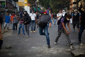 Demonstrators throw rocks at police during a protest in Caracas.