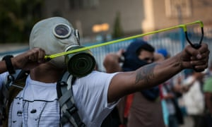 A student takes aim against the police in Caracas.