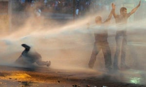Supporters of opposition leader Leopoldo López are hit by police's water canon during a protest against Nicolás Maduro's government in Caracas.