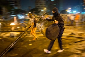 A masked demonstrator carries a barrel to build a road block in the Altamira neighborhood of Caracas.