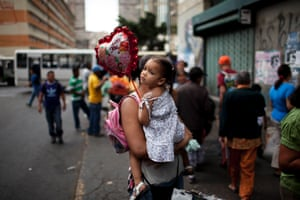 Maria Ramirez holds a balloon in the arms of her mother in downtown Caracas as demonstrators gather on the street in support of opposition leader Leopoldo López.