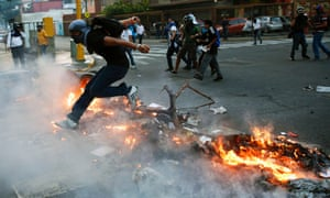 A supporter of opposition leader Leopoldo López jumps over a burning barricade in Caracas.