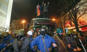 Protesters in Kiev guard a bus holding captured police who were later allowed to go home.