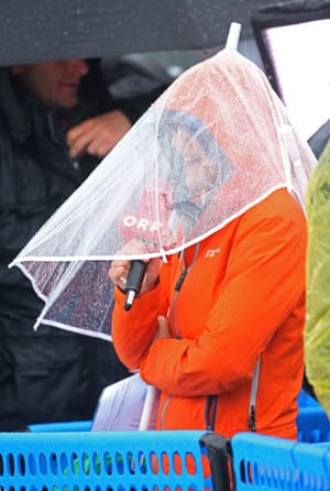 A spectator shelters from the rain during the Freestyle Skiing Womens' Ski Cross Seeding at the 2014 Winter Olympics.