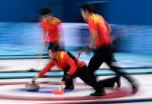 China's skip, Liu Rui, delivers the stone to sweepers Zang Jialiang, left, and Ba Dexin during the men's curling bronze medal game against Sweden.