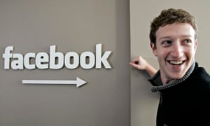 Mark Zuckerberg CEO of Facebook stands next to a Facebook sign smiling