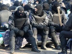 Riot police sit near the Ukrainian parliament in Kiev.