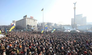 People listen to police officers from Lviv who have joined anti-government protesters as they speak from a stage during a rally in Independence Square in Kiev on 21 Febuary 2014.