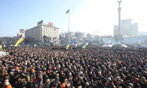 People listen to police officers from Lviv who have joined anti-government protesters as they speak from a stage during a rally in Independence Square in Kiev.