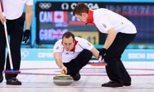 Michael Goodfellow of Great Britain (C) plays a stone as Scott Andrews (L) and Greg Drummond (R) assist.