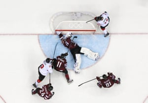 Latvia Goalkeeper Kristers Gudlevskis tries to save a shot from Canada's Patrick Marleau.