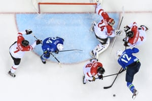 Slovenia's David Rodman tries to score against Austria but the puck is repelled.