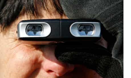 A woman looks through binoculars
