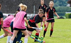 Teenage girls playing hockey