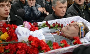 The body of an anti-government demonstrator killed in clashes with police is carried through the crowd in Independence square.