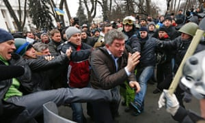Anti-government protesters attack a deputy of the Party of Regions Vitaly Grushevsky outside the Ukrainian Parliament building in Kiev.