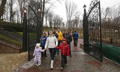 People walk on the grounds of the Mezhyhirya residence of Ukraine's President Viktor Yanukovich in the village Novi Petrivtsi outside Kiev February 22, 2014.