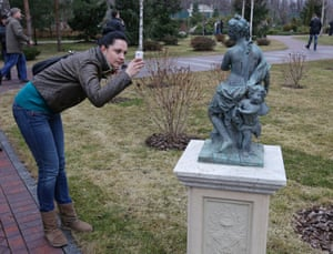 A woman takes a picture of a statue in the Presidential gardens.