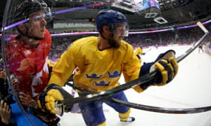 Canada's Corey Perry and Alexander Edler of Sweden compete for the puck along the boards during the Men's Ice Hockey Gold Medal match at the 2014 Sochi Winter Olympics.