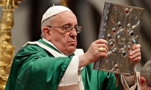 Pope Francis holds the book of the gospels aloft