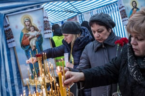 Women light candles in a tent serving as makeshift chapel on Independence Square