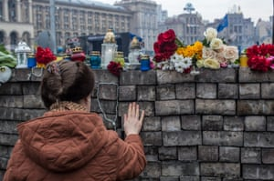 A woman pays her respects at a barricade erected by anti-government protesters