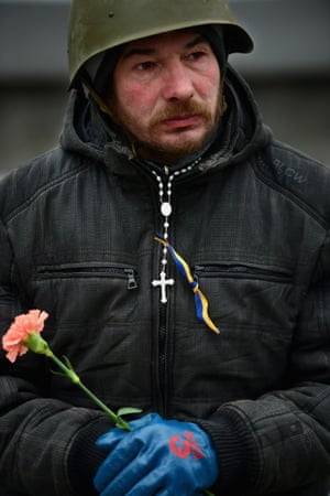 A protester in a helmet carries a flower in Independence Square