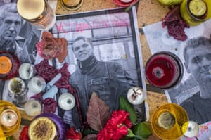 Candles and flowers are placed among images of killed anti-government protesters