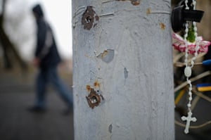 Rosary beads and flowers are left beside a bullet marked lamp post in Independence Square