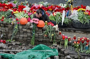 A mourner leaves flowers at a barricade