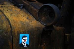 A sticker depicting Ukrainian President Viktor Yanukovych is placed on a burned military truck in Kiev
