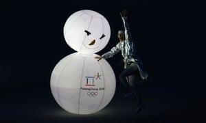 在2014年冬季奥运会闭幕式上,一位艺术家在下一届冬季奥运会移交平昌后,在一个点燃的雪人附近表演。