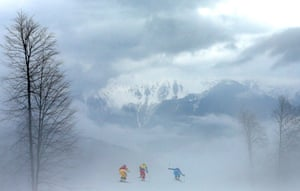 Anna Holmlund of Sweden, Stephanie Joffroy of Chile and Katrin Ofner of Austria compete in heavy fog in the freestyle skiing women's ski cross quarter-finals.
