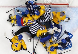 Officials attempt to separate players in the goal crease after a stoppage in play during a men's play-off semi-final ice hockey game.