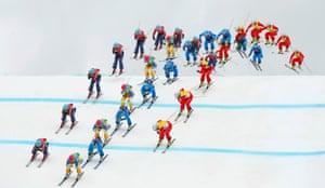 Sweden's Anna Holmlund (green bib), Canada's Kelsey Serwa (red bib), Austria's Katrin Ofner (blue bib) and Switzerland's Fanny Smith (yellow bib) compete during the women's freestyle ski-cross semi-finals.
