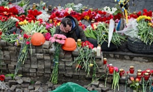 A mourner lays flowers at a makeshift memorial in Kiev