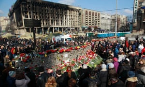 People lay flowers at barricades in memory of the victims of the recent clashes in central Kiev 24 February, 2014.