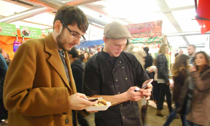 Alex Hern (l) and Olivier Rynkiewicz (r) making a payment in dogecoin for a burger.