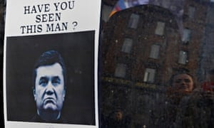 Ukrainians look at a 'wanted' notice for fugitive president Victor Yanukovych in Kiev.