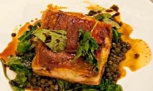 A slice of lamb belly on lentils with greens