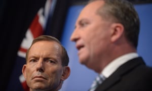 Prime Minister Tony Abbott listens to Agriculture minister Barnaby Joyce speaking to the media during a press conference at Parliament House in Canberra, Wednesday, Feb. 26, 2014. Mr Abbott and Mr Joyce announced a drought relief package.