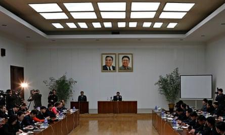 Kim Jeung-wook seated beneath the portraits of late North Korean leaders Kim Il-sung and Kim Jong-il