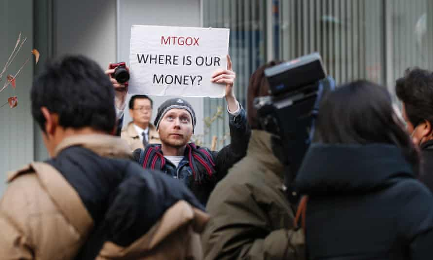 Kolin Burges, a self-styled cryptocurrency trader and former software engineer from London, holds up a placard to protest against Mt. Gox outside the company's Tokyo headquarters.