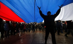 Pro-Russian demonstrators march with a huge Russian flag during a protest in front of a local government building in Simferopol, Crimea, Ukraine.