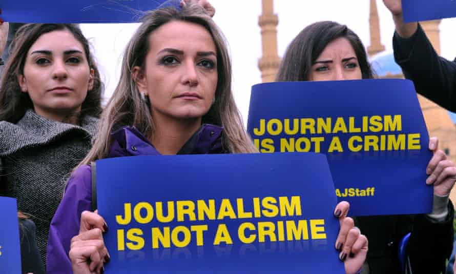 Lebanese journalists and activists hold placards to show their solidarity with detained Al-Jazeera staff in Egypt
