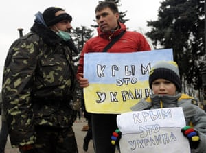 "People hold placards reading ""Crimea is Ukraine"" during a rally in front of the Ukrainian parliament in Kiev on February 27, 2014."