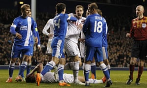 Tottenham Hotspur's English defender Michael Dawson reacts after an incident leaves his team-mate Jan Vertonghen on the ground. Dnipro's Roman Zozulya was sent off for an invented head-butt.